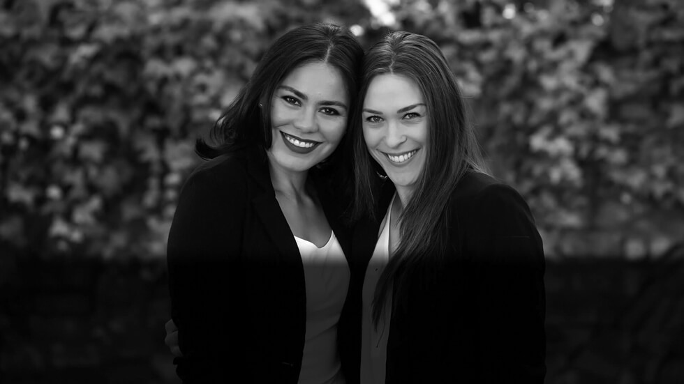 Our two beautiful dental assistants smiling standing outside the office while they are hugging