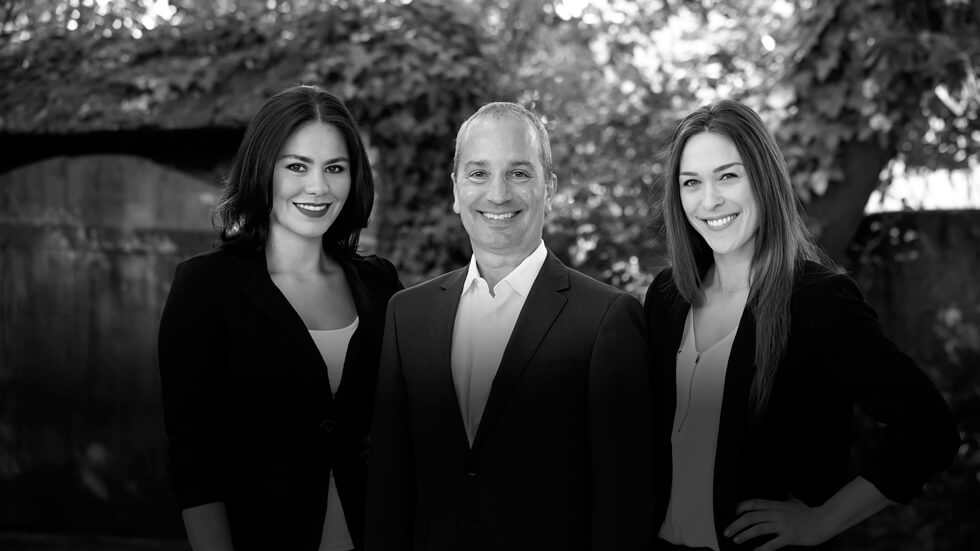 Dr. Santucci with his two assistants: Marisa Beetz and Jenna standing outside the office smiling while dressed in suits