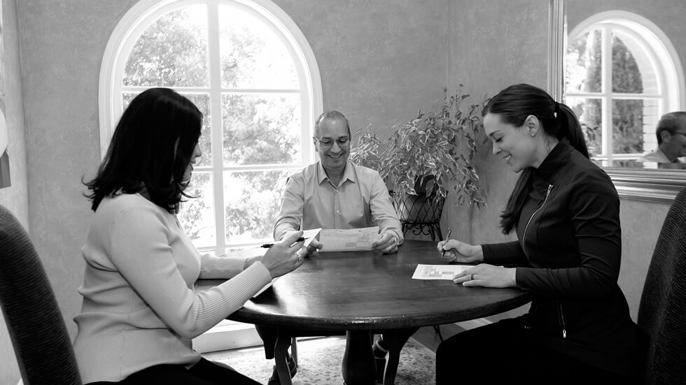 Dr. Santucci inside the dental office sitting at a table with his two female dental assistants checking some papers while smiling