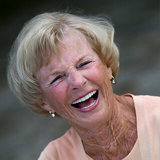Sue, an elderly female patient of Doctor Santucci smiling while wearing two gold earrings