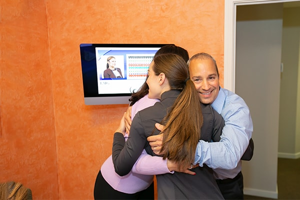 Dr. Santucci inside the dental office hugging two of his dental assistants while smiling