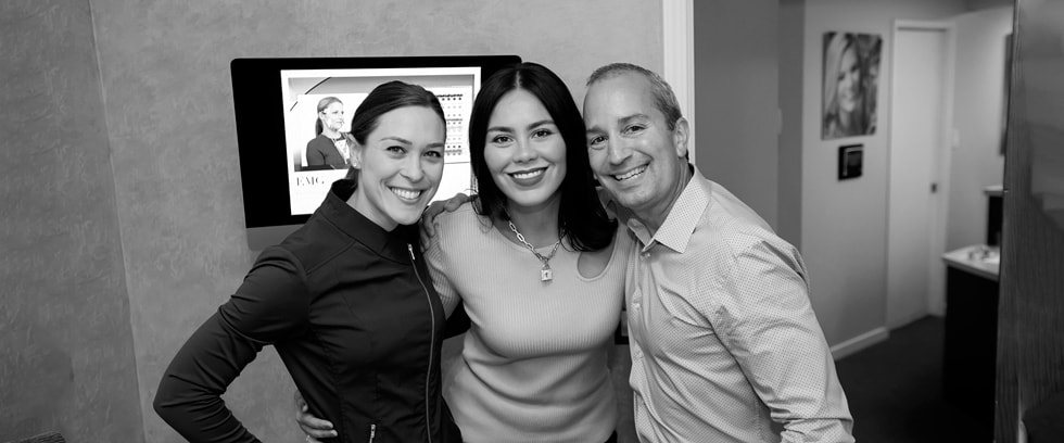 Dr. Santucci with his two female assistants inside the dental office standing, smiling and hugging while they look straight ahead